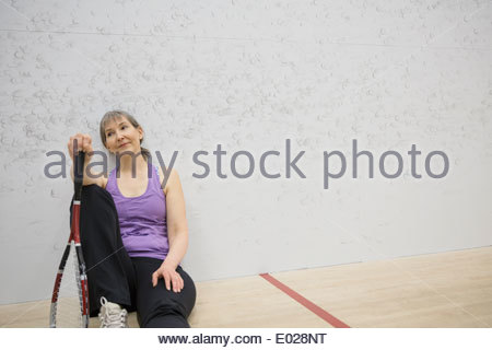 Woman resting on indoor squash court - Stock Photo