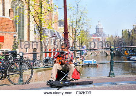 Busker playing guitar on a sunny afternoon in Amsterdam's Red Light District, Noord Holland, Netherlands - Stock Photo
