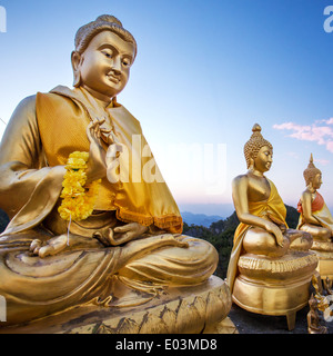 Golden Buddha statues on the top of the mountain in Tiger Temple in Krabi, Thailand - Stock Photo