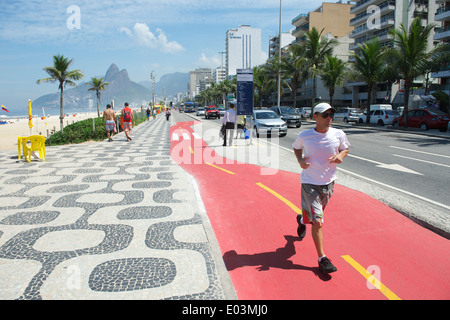 RIO DE JANEIRO, BRAZIL - APRIL 1, 2014: Jogger runs along boardwalk bike path on Avenida Vieira Souto in Ipanema, - Stockfoto