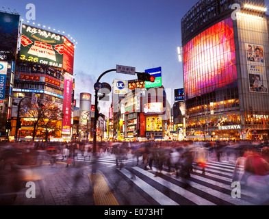 Crowd of people crossing Meiji dori street at Shibuya station lit with colorful signs during sunset. Shibuya, Tokyo, - Stock Photo