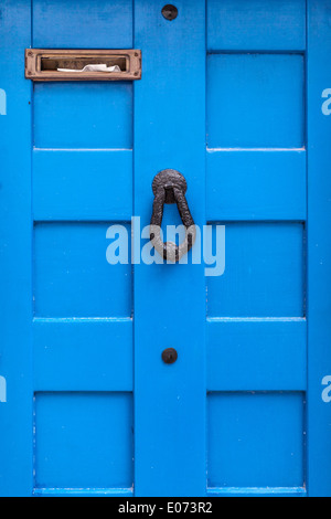 a blue wooden door with a door knocker and a full letter box - Stock Photo