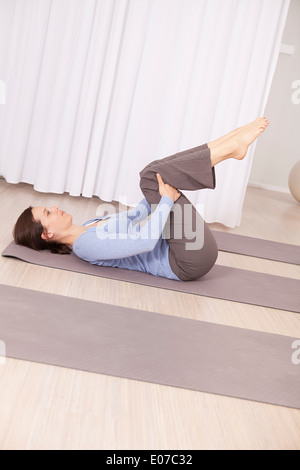 mature woman doing pilates exercise on fitness ball stock
