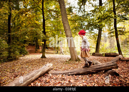 Full length of girl walking on log in forest - Stock Photo