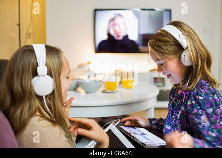 Happy sisters listening music on digital tablets in living room - Stock Photo