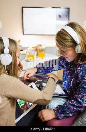 Sisters listening music on digital tablets in living room - Stock Photo