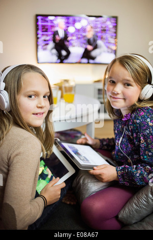 Portrait of smiling sisters listening music on digital tablets in living room - Stock Photo