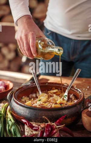 Man preparing fish dish, adding olive oil - Stock Photo