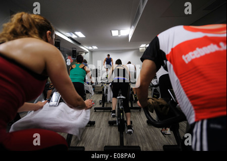 View from the back of people riding stationary bicycle during a spinning class at the gym - Stock Photo