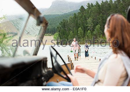 Woman sitting in vehicle near lake - Stock Photo