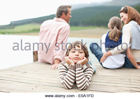 Family sitting on pier by lake - Stock Photo