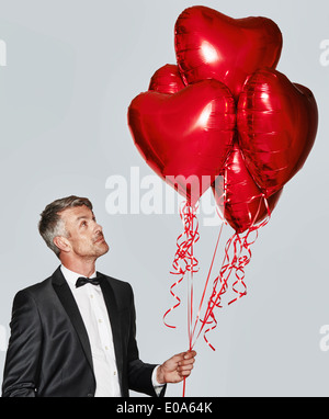 Portrait of man in tuxedo with heart-shaped balloons - Stockfoto