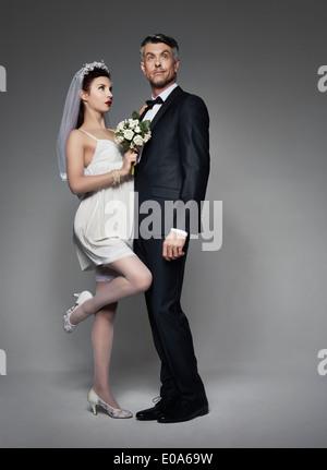 Bridegroom with bride in burlesque style costume - Stock Photo
