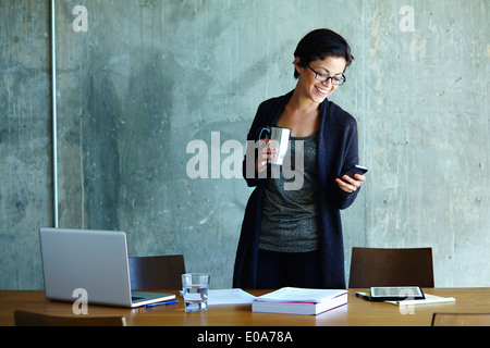 Young businesswoman looking at smartphone in office - Stock Photo