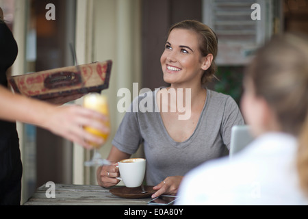 Two young adult female friends ordering from menu in cafe - Stock Photo