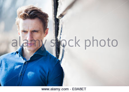 Mid adult man leaning against wall - Stock Photo