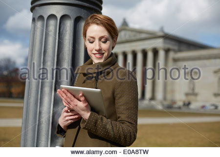 Woman using digital tablet, monument in background, Munich, Germany - Stock Photo