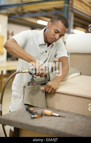 Upholsterer attaching textile to frame using staple gun - Stock Photo
