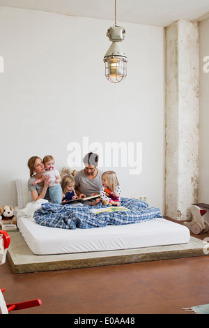 Family with three daughters reading books in bed - Stock Photo