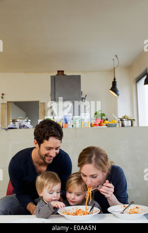 Family with two daughters eating spaghetti meal - Stock Photo