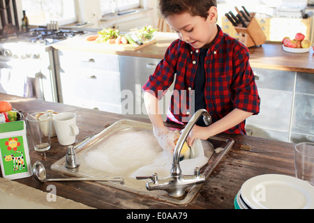 Young boy washing up in kitchen - Stock Photo