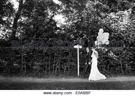 B&W image of mid adult bride and groom walking in garden - Stock Photo
