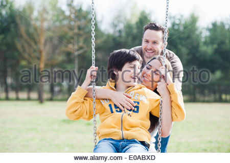 Parents hugging son on park swing - Stock Photo