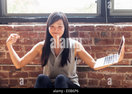 Mid adult woman sitting on floor balancing laptop on arm - Stock Photo