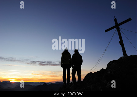 Young woman and young man enjoying sunset at summit of Risserkogel, Bavarian Prealps, Mangfall Mountains, Bavaria, - Stock Photo