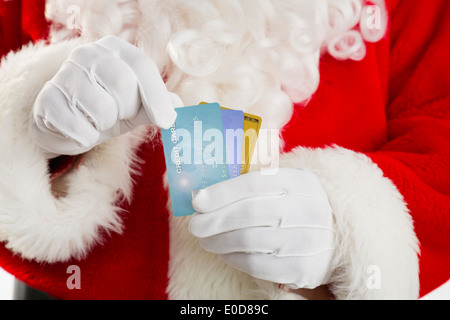 Mid section of Santa holding credit cards - Stock Photo
