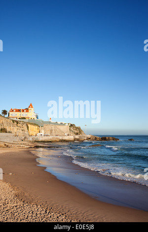 Sunset time at a beach with a cliff on Atlantic Ocean coast in resort town of Estoril in Portugal. - Stock Photo