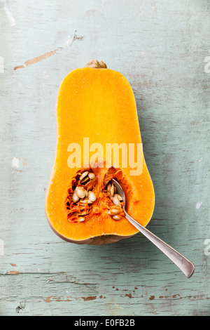 Half cut of ripe butternut squash on blue background - Stock Photo