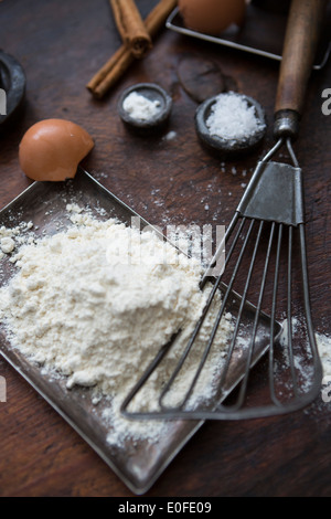Ingredients for making pancakes, including eggs, flour cinnamon and a batterwhip - Stock Photo