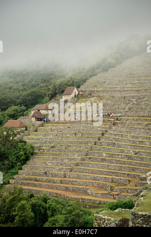 Tourists with plastic rain coats on the terraces of Machu Picchu, Cusco, Cuzco, Peru, Andes, South America - Stock Photo