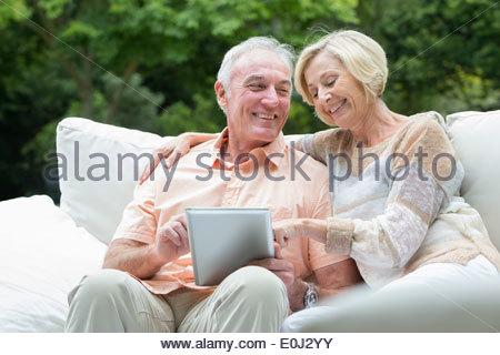 Senior couple using digital tablet on outdoor sofa - Stock Photo
