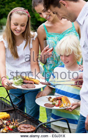 Happy family standing at barbecue grille - Stock Photo
