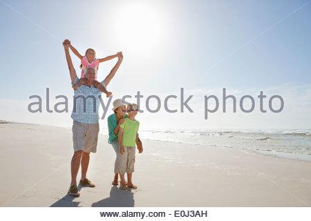 Grandparents and grandchildren walking on sunny beach - Stock Photo