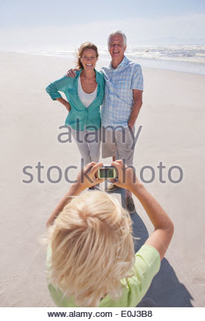 Grandson with digital camera photographing grandparents on sunny beach - Stock Photo