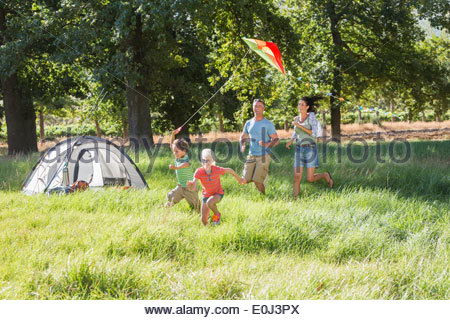 Family Flying Kite On Camping Holiday In Countryside - Stock Photo