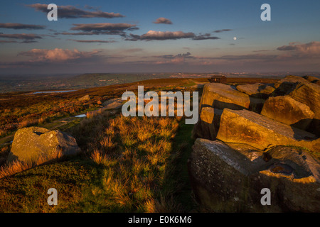 View of the moor and over to Leeds Bradford Airport with the moon rising and the sun setting, UK - Stock Photo