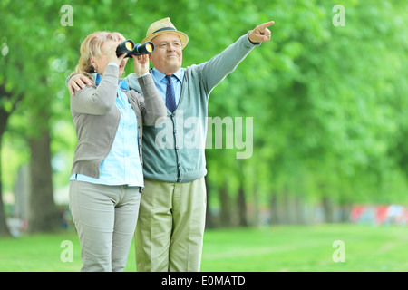 Woman looking through binoculars with her husband in park - Stock Photo