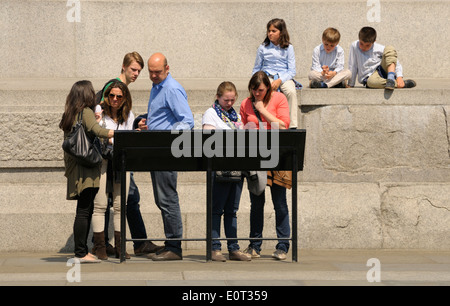 London, England, UK. Family looking at information board by Nelson's Column - Stock Photo