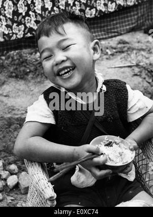 Young Vietnamese boy eats in Saigon - Stock Photo