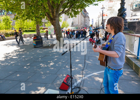 Busker playing acoustic guitar on the London embankment - Stock Photo