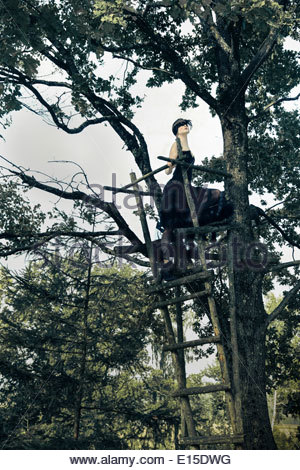 Germany, Blindfolded woman on raised hide in tree - Stock Photo