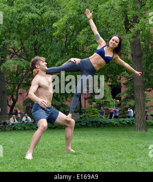An athletic fit couple do balancing exercises in Washington Square Park in New York City - Stockfoto
