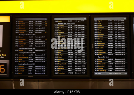 flight information boards London Heathrow Airport Terminal 5 early in the morning UK - Stock Photo