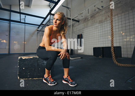 Young woman sitting on a box at gym after her workout. Caucasian female athlete taking rest after exercising at - Stock Photo