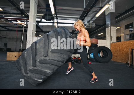 Muscular young woman flipping tire at gym. Fit female athlete performing a tire flip at crossfit gym. - Stock Photo