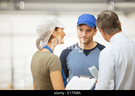 Supervisor and workers talking in food processing plant - Stock Photo